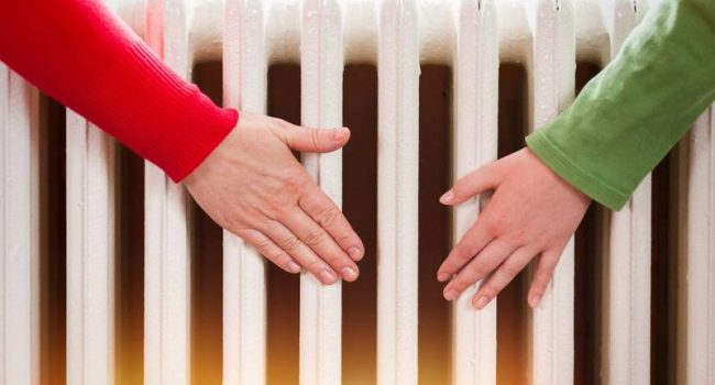 two hands touching the radiator to check whether heated